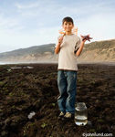 Picture of a boy holding a net over his shoulder and a starfish in his hand at low tide at the ocean. The boy is smiling and proudly looking at the camera. At this feet is a large glass jar with water in it.